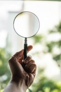 human-hand-holding-magnifying-glass