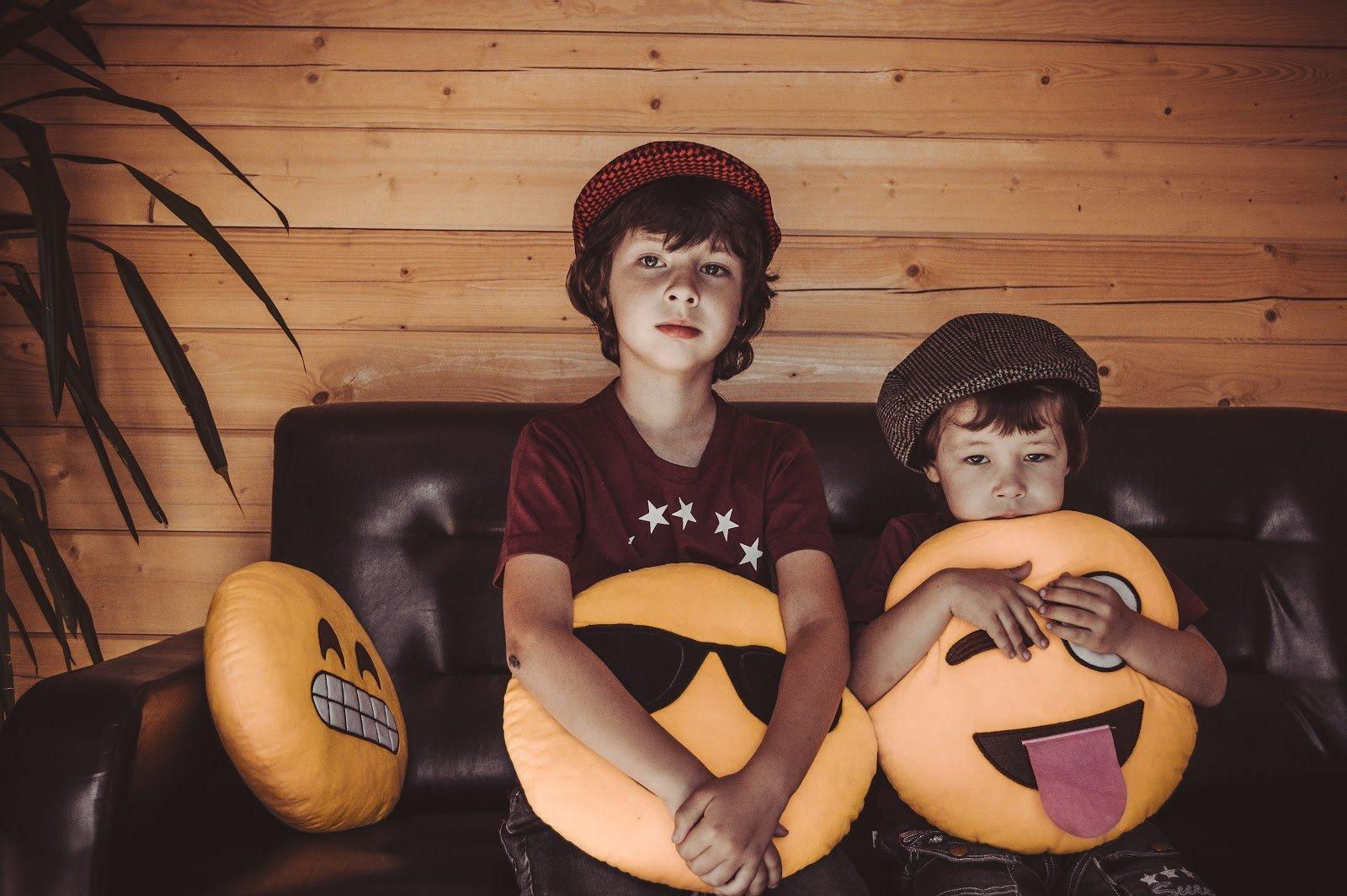 two-boys-sitting-on-sofa-holding-emoji-throw-pillows