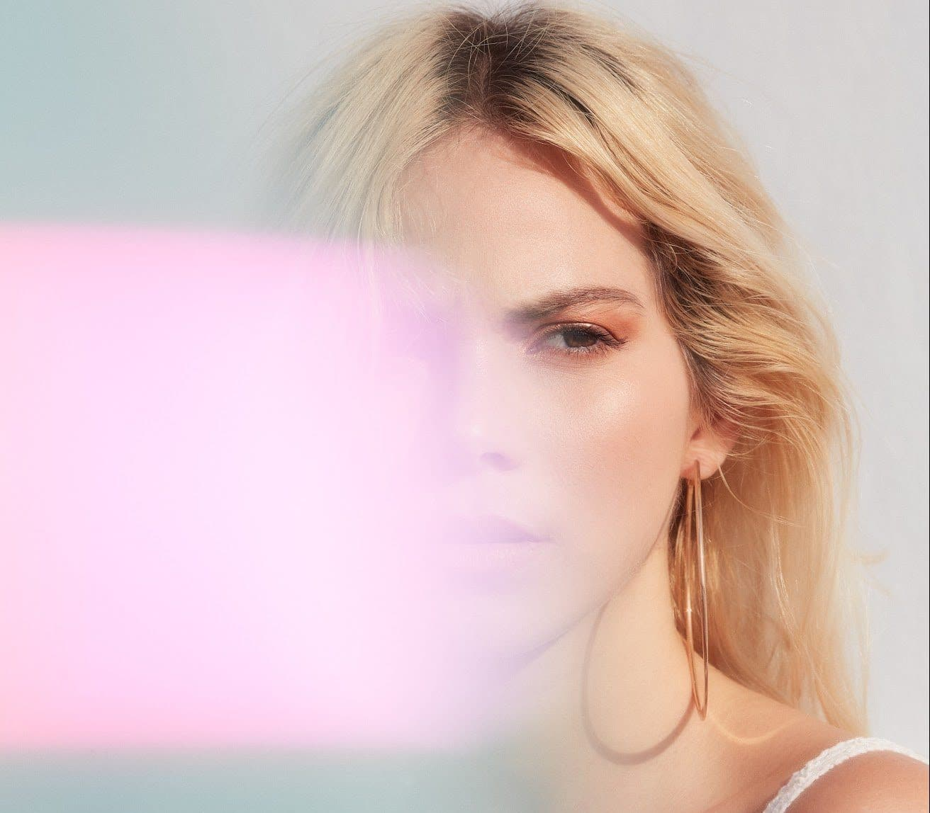 portrait-of-blonde-woman-with-pink-lens-flare-covering-half-of-her-face