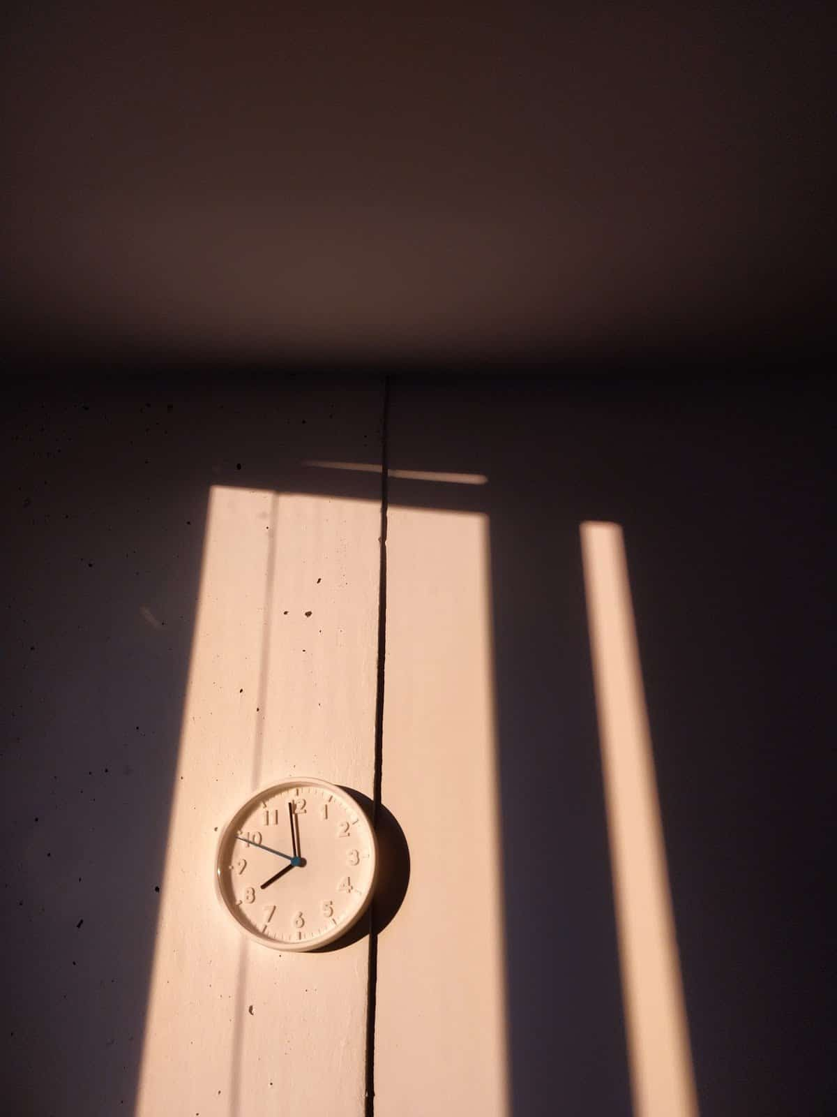 white-clock-on-white-wall-with-heavy-shadows