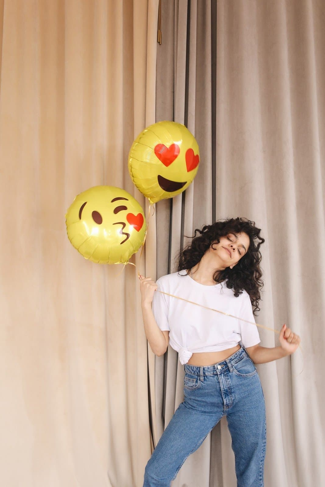 woman-in-white-shirt-and-blue-denim-pants-holding-yellow-emoji-balloons