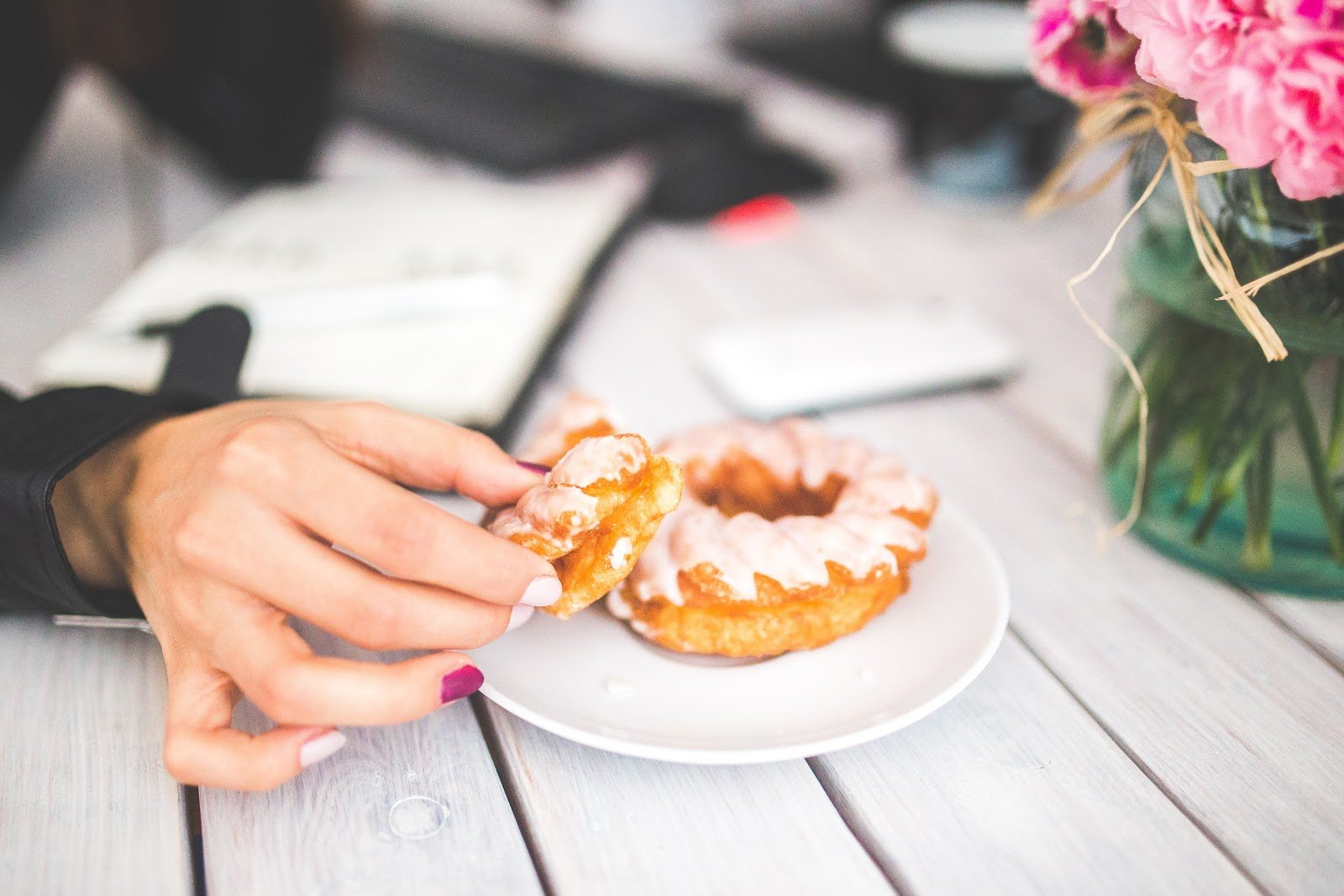 womans-hand-with-painted-nails-holding-frosted-donuts