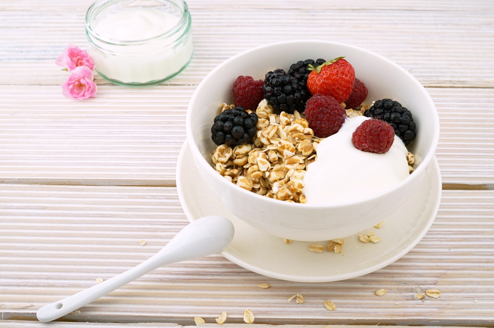 granola-and-yoghurt-with-strawberry-blueberries-and-raspberries-in-white-ceramic-bowl
