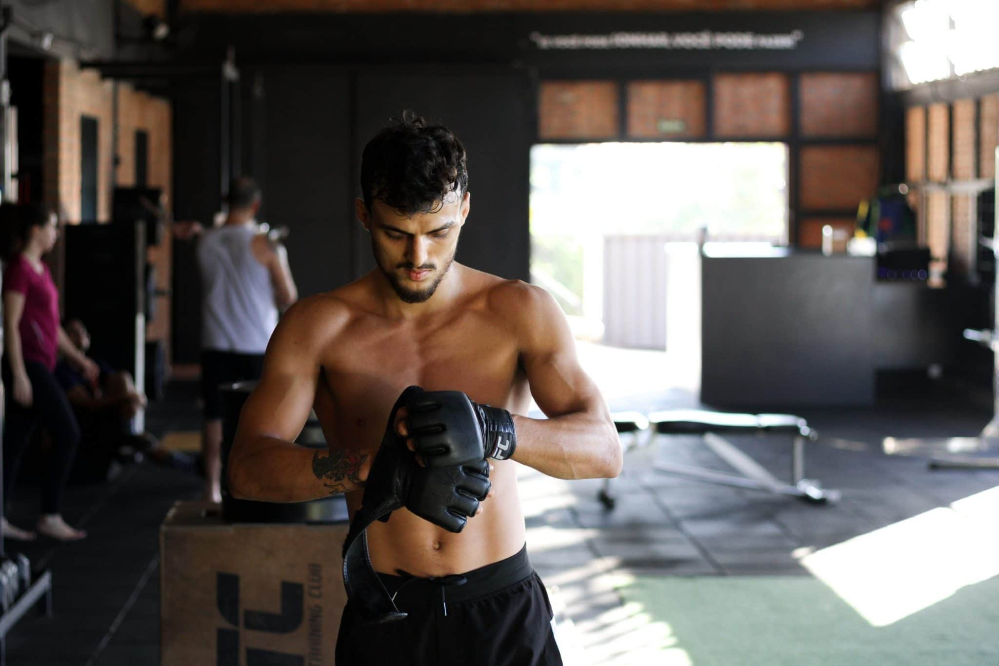 man-standing-in-gym-wearing-black-boxing-gloves
