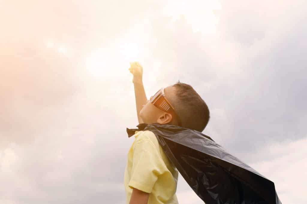 young-boy-wearing-superhero-costume-raising-his-fist-to-the-clouds