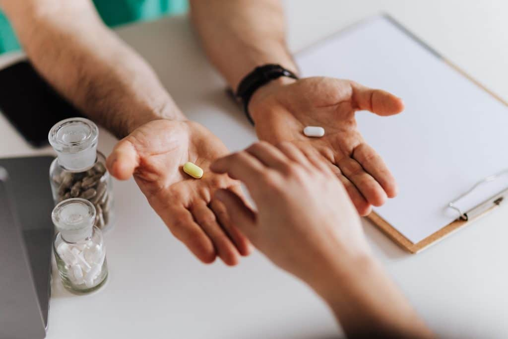 doctor-holding-two-pills-out-in-palm-of-hands