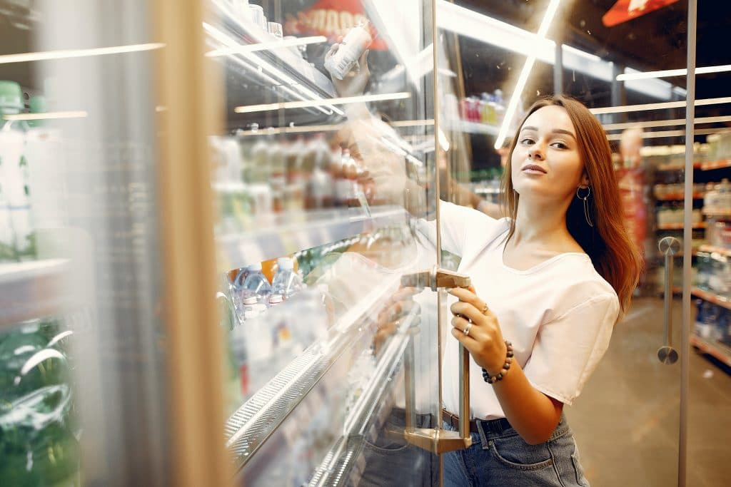 young-woman-choosing-drink-from-refrigerator