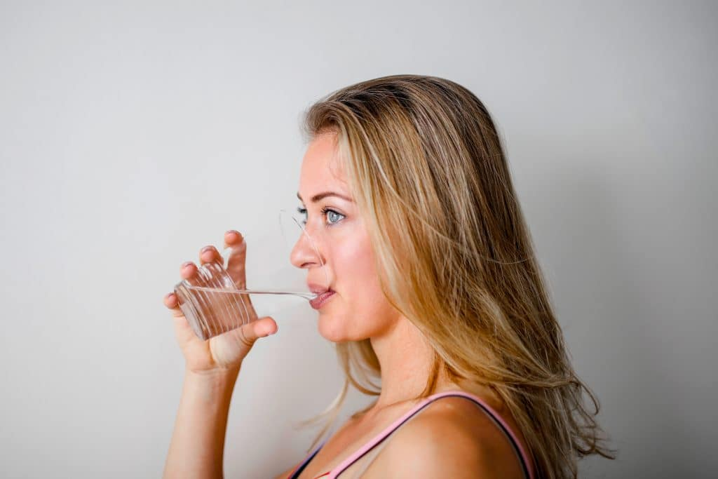 profile-of-a-blonde-woman-drinking-water-from-a-clear-cup