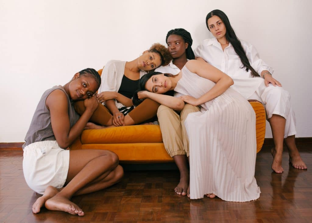 five-women-sitting-together-on-an-orange-couch