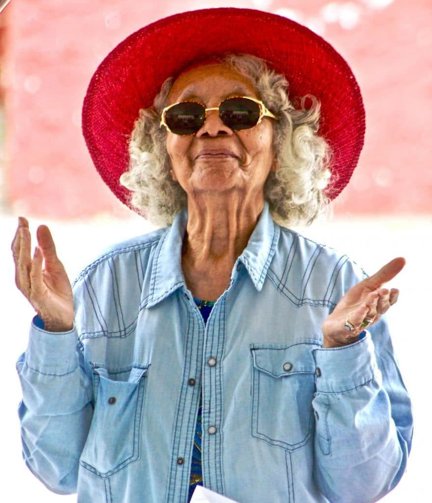 senior woman in red hat holding her hands up in a peaceful pose