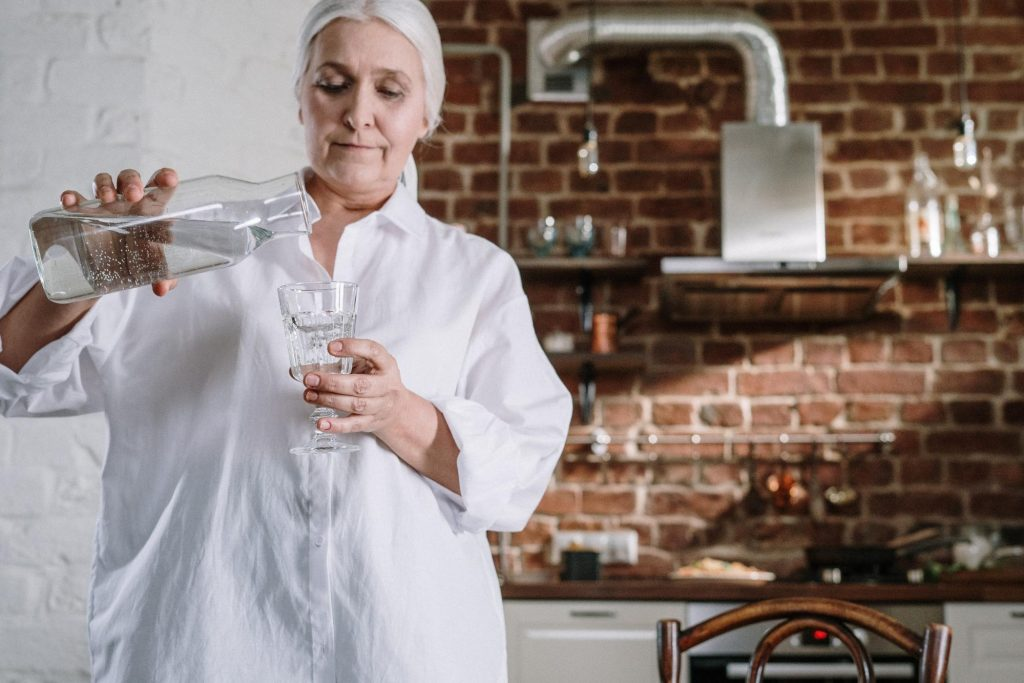 senior woman in her kitchen pouring herself glass of water