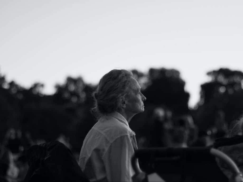 black and white photo of a senior woman sitting on a park bench facing away form the camera