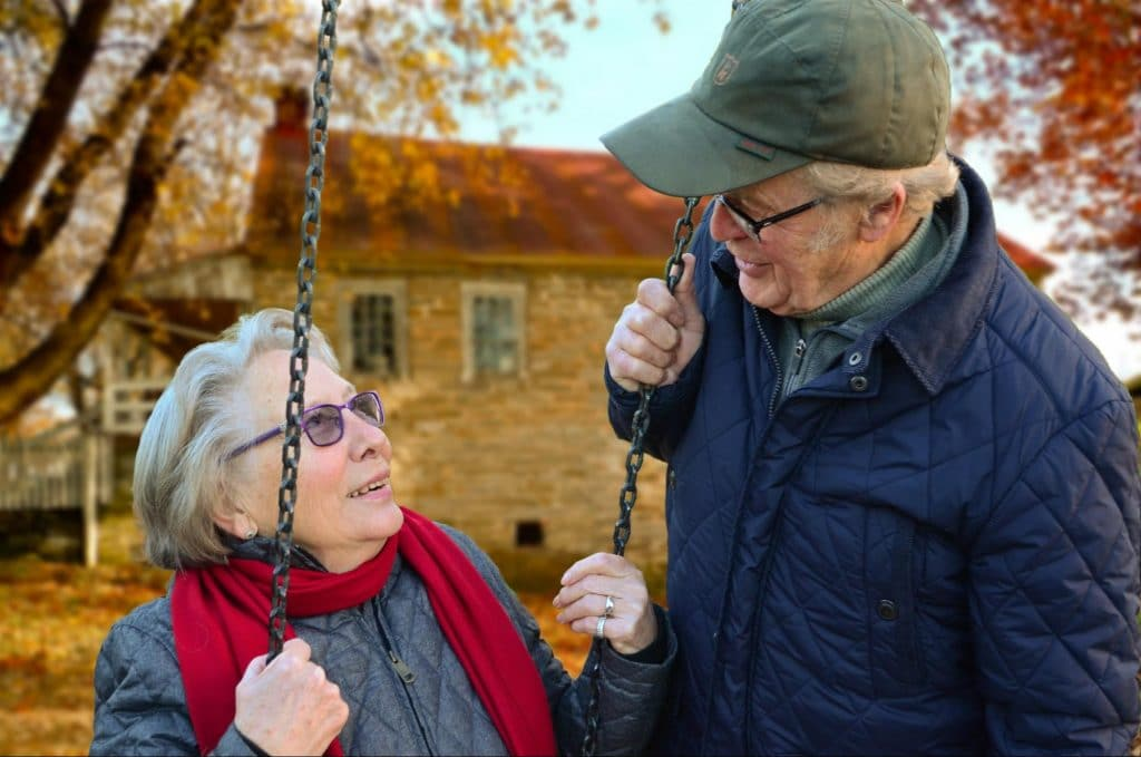 senior couple smiling and laughing at one another on a swingset in a park