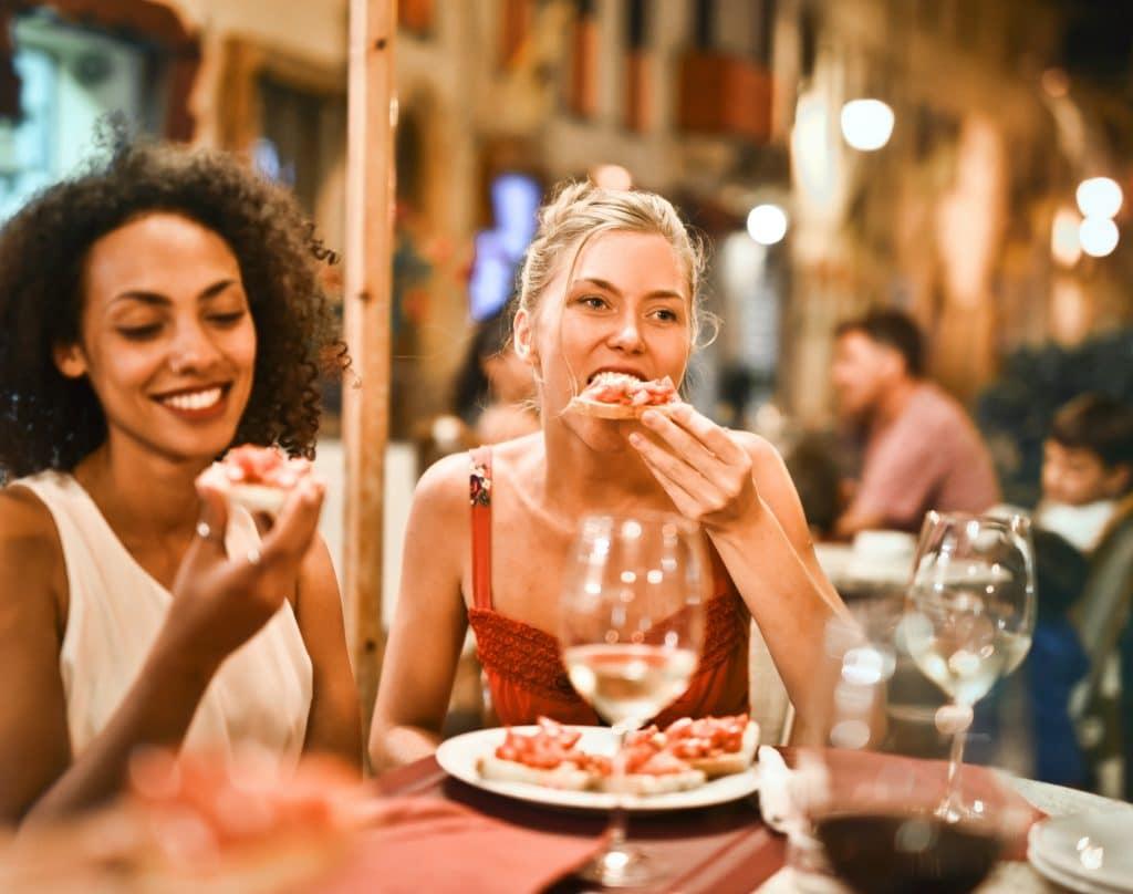 two women eating bruschetta