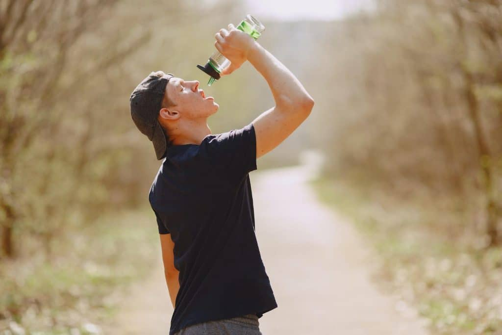 man drinking water from a bottle to rehydrate while on a walk