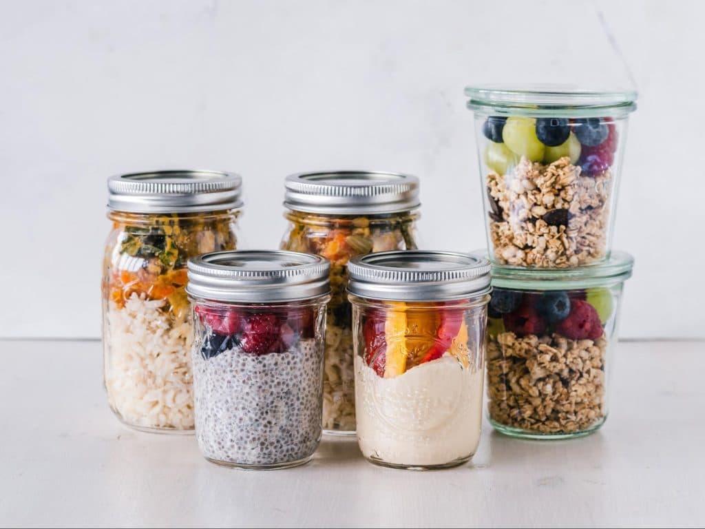 Prebiotic foods including berries and fiber and probiotic foods like yogurt in meal prep jars