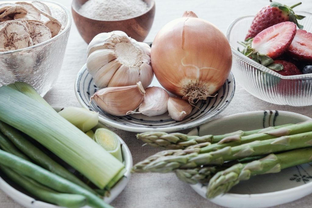 An assortment of prebiotic foods including garlic, strawberries, onions, leeks, and asparagus.