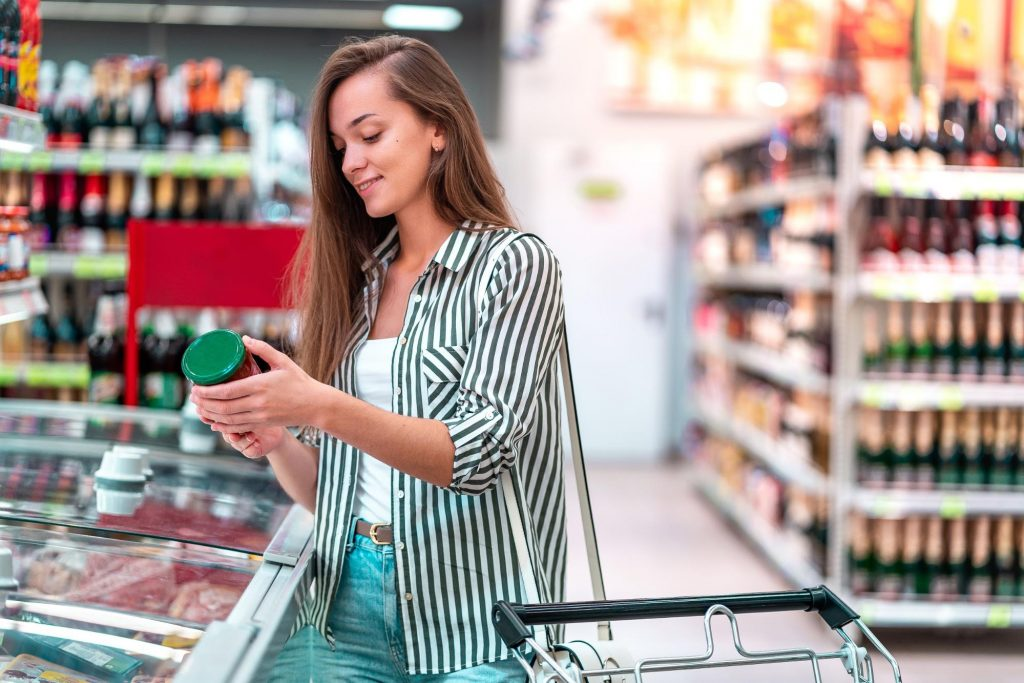 A woman reads nutritional labels in a grocery store to see if she can find foods with prebiotics in them.