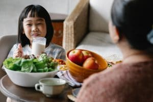 A happy child and her mother eat a meal together with a good mix of probiotic and prebiotic foods including apples and leafy greens.
