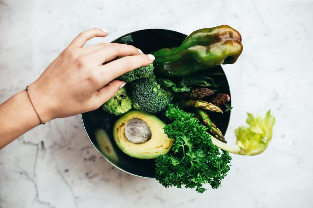 Healthy green vegetables including artichokes, avocados, broccoli, kale, and bell peppers in a bowl. Some of these vegetables are excellent sources of prebiotic fiber which are helpful for the good bacteria in the gut.