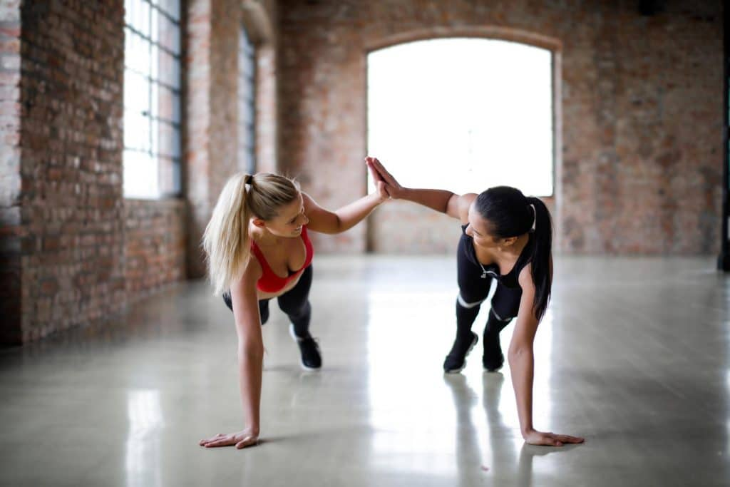 Two athletes high five as they stretch. Having a good balance of probiotics supported by prebiotics along with regular exercise can help support a healthy gut.