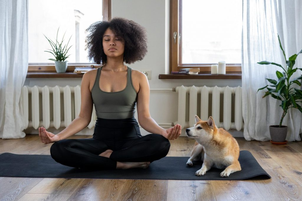 Woman in yoga pose with a dog sitting next to her. Regular exercise and a healthy diet full of prebiotic and probiotic foods can help with weight loss.