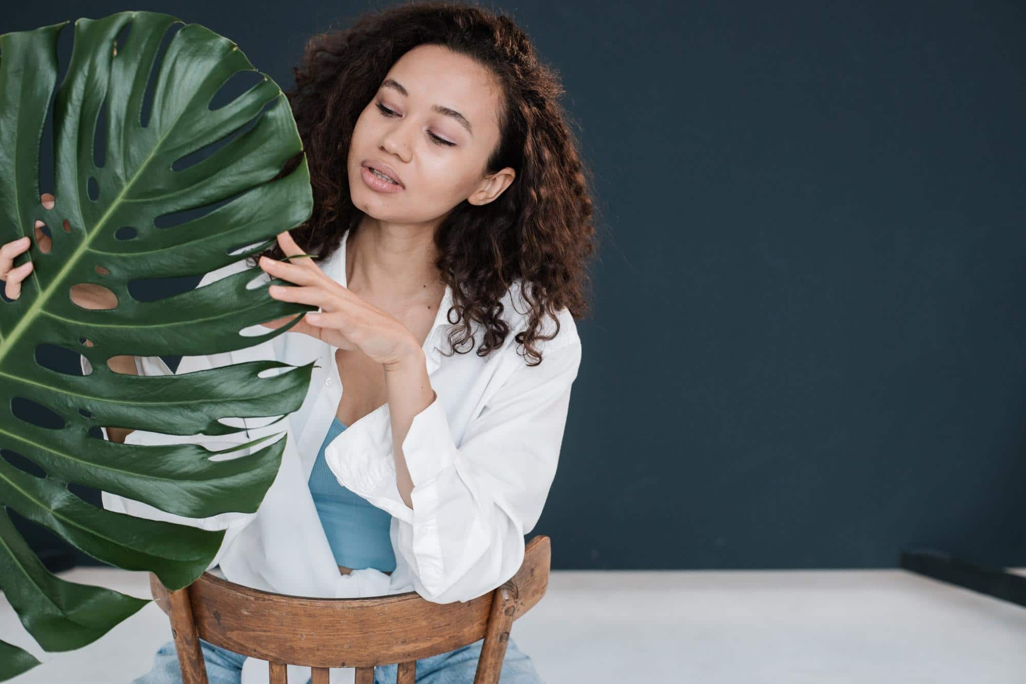 Photo of a healthy young woman sitting In a chair touching a plant. Taking prebiotics can help support the good bacteria in your gut and reinforce overall health.