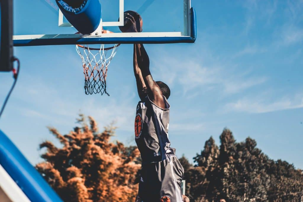 A healthy man does a slam dunk while playing basketball. Proper nutrition and a balanced gut with prebiotics and probiotics can help people with an active and healthy lifestyle.