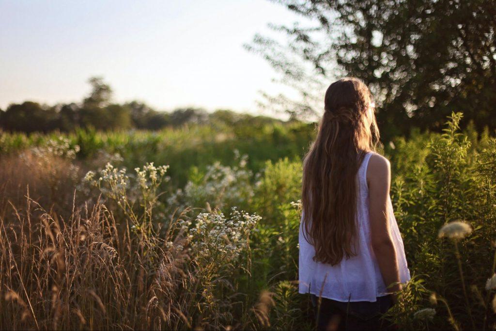 A woman in a white shirt walks through a meadow.