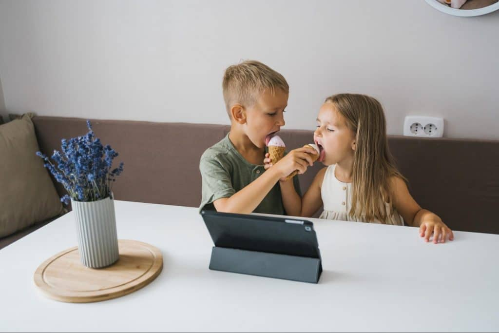 Two kids eating ice cream and using tablet computer.