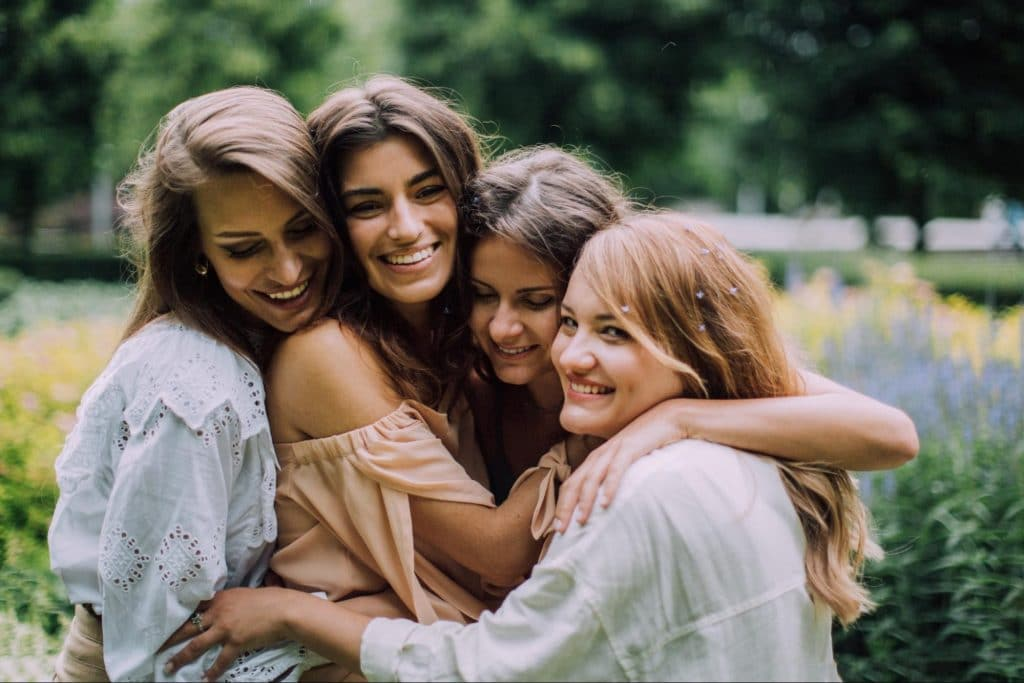 Four healthy young women group hug.