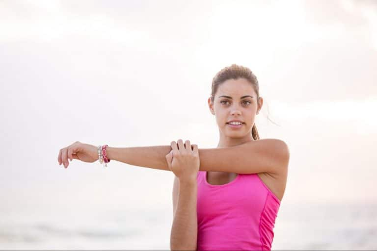 Woman in pink shirt stretching before exercise.