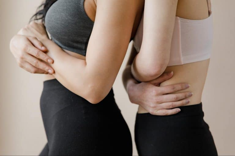 Two women standing back to front holding their stomachs