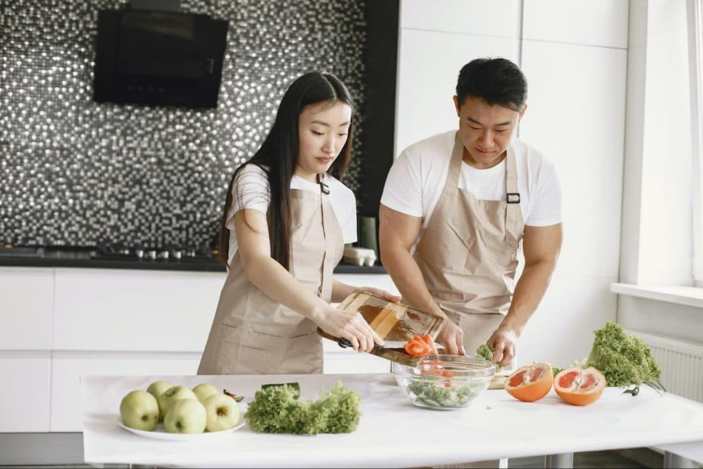 couple making salad on counter