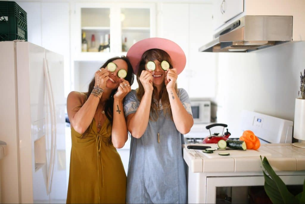 Two women smiling with cucumbers over their eyes.
