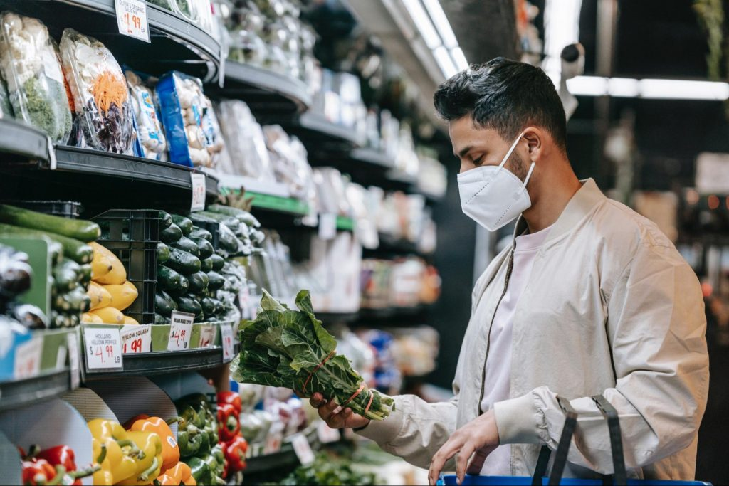 Man in grocery store looking at vegtables.