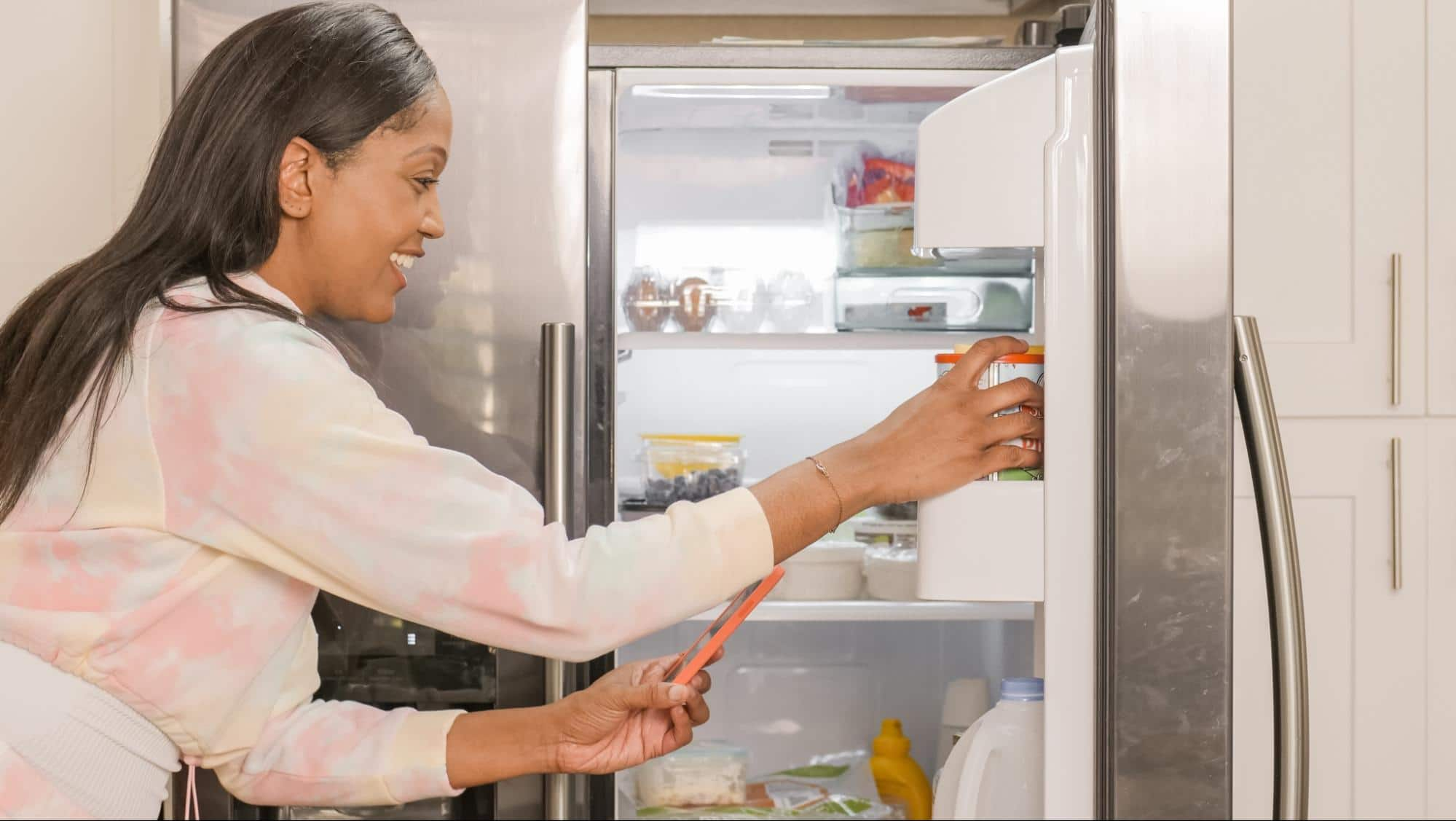Black Woman getting in refrigerator, reaching for yogurt